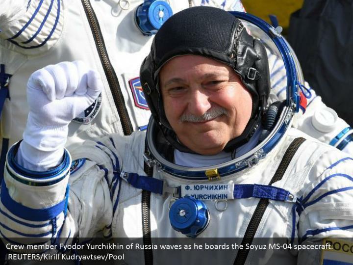 Crew member Fyodor Yurchikhin of Russia waves as he boards the Soyuz MS-04 spacecraft.   REUTERS/Kirill Kudryavtsev/Pool