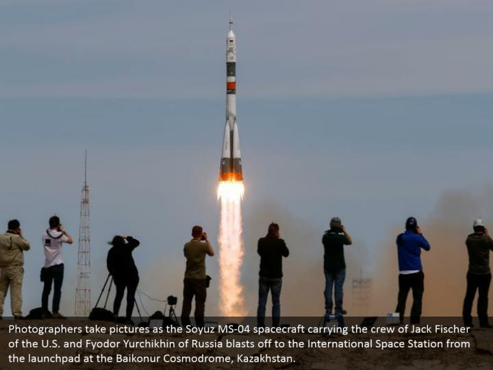 Photographers take pictures as the Soyuz MS-04 spacecraft carrying the crew of Jack Fischer of the U.S. and Fyodor Yurchikhin of Russia blasts off to the International Space Station from the launchpad at the Baikonur Cosmodrome, Kazakhstan.