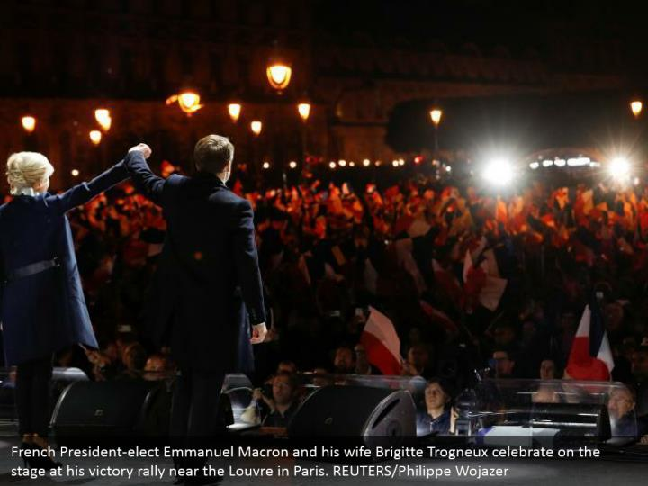 French President-elect Emmanuel Macron and his wife Brigitte Trogneux celebrate on the stage at his victory rally near the Louvre in Paris. REUTERS/Philippe Wojazer