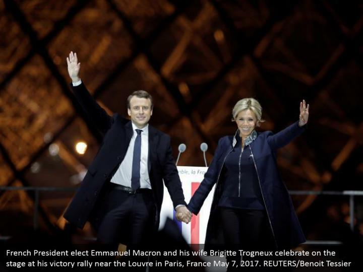 French President elect Emmanuel Macron and his wife Brigitte Trogneux celebrate on the stage at his victory rally near the Louvre in Paris, France May 7, 2017. REUTERS/Benoit Tessier