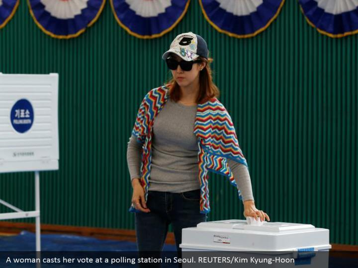 A woman casts her vote at a polling station in Seoul. REUTERS/Kim Kyung-Hoon