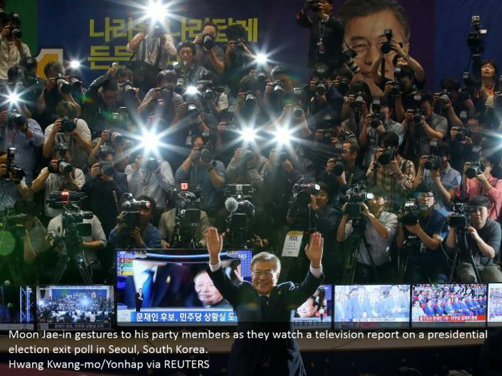Moon Jae-in gestures to his party members as they watch a television report on a presidential election exit poll in Seoul, South Korea.  Hwang Kwang-mo/Yonhap via REUTERS