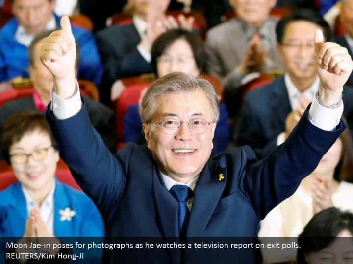 Moon Jae-in poses for photographs as he watches a television report on exit polls. REUTERS/Kim Hong-Ji