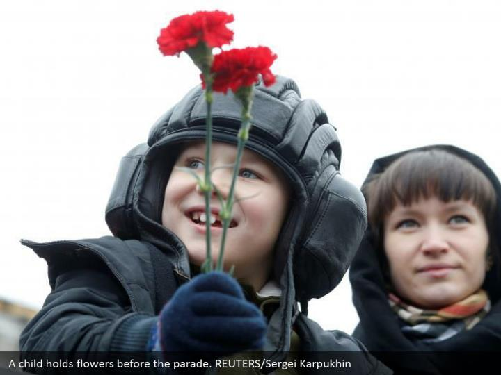A child holds flowers before the parade. REUTERS/Sergei Karpukhin