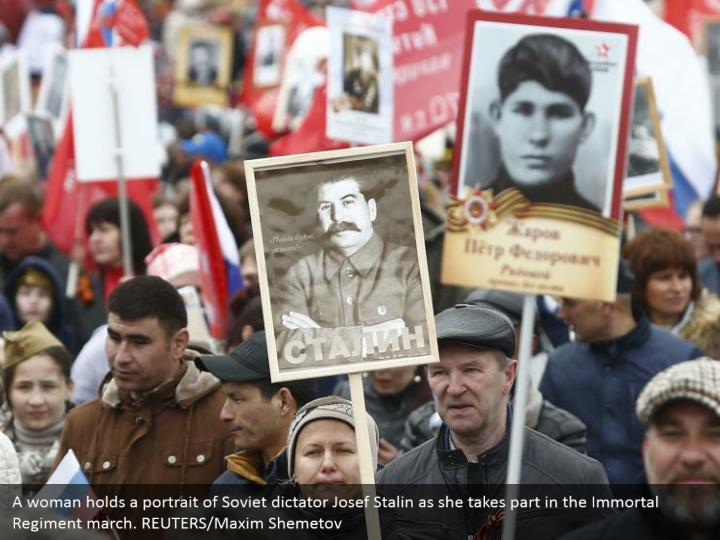 A woman holds a portrait of Soviet dictator Josef Stalin as she takes part in the Immortal Regiment march. REUTERS/Maxim Shemetov