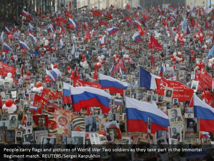 People carry flags and pictures of World War Two soldiers as they take part in the Immortal Regiment march. REUTERS/Sergei Karpukhin