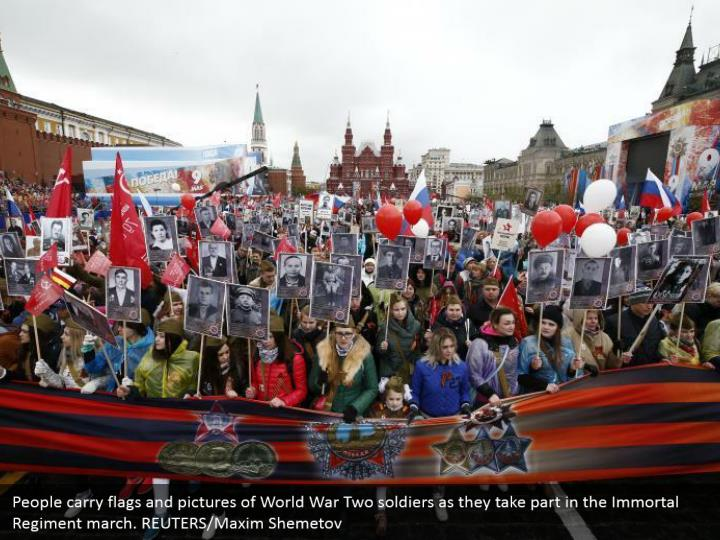 People carry flags and pictures of World War Two soldiers as they take part in the Immortal Regiment march. REUTERS/Maxim Shemetov