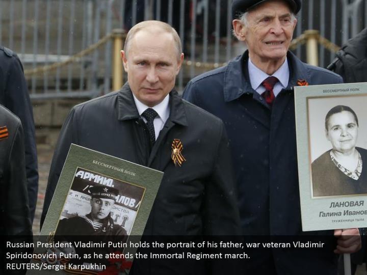 Russian President Vladimir Putin holds the portrait of his father, war veteran Vladimir Spiridonovich Putin, as he attends the Immortal Regiment march. REUTERS/Sergei Karpukhin