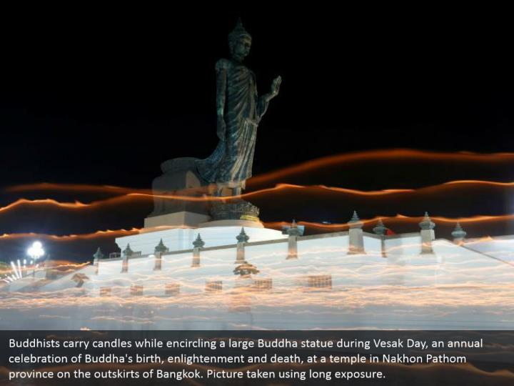 Buddhists carry candles while encircling a large Buddha statue during Vesak Day, an annual celebration of Buddha's birth, enlightenment and death, at a temple in Nakhon Pathom province on the outskirts of Bangkok. Picture taken using long exposure.