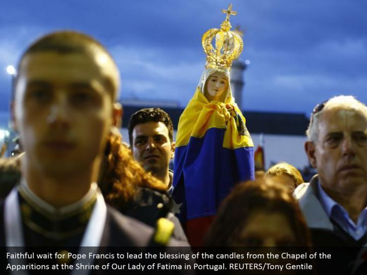 Faithful wait for Pope Francis to lead the blessing of the candles from the Chapel of the Apparitions at the Shrine of Our Lady of Fatima in Portugal. REUTERS/Tony Gentile
