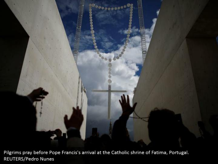 Pilgrims pray before Pope Francis's arrival at the Catholic shrine of Fatima, Portugal. REUTERS/Pedro Nunes