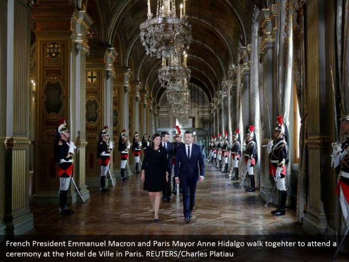 French President Emmanuel Macron and Paris Mayor Anne Hidalgo walk togehter to attend a ceremony at the Hotel de Ville in Paris. REUTERS/Charles Platiau
