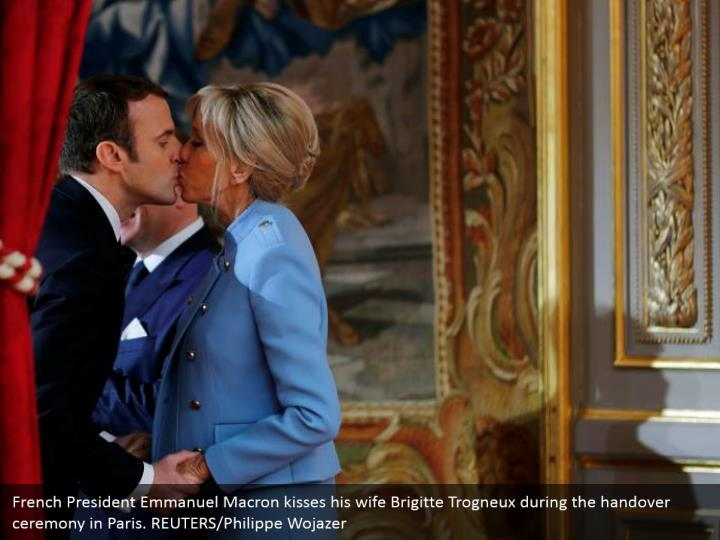 French President Emmanuel Macron kisses his wife Brigitte Trogneux during the handover ceremony in Paris. REUTERS/Philippe Wojazer