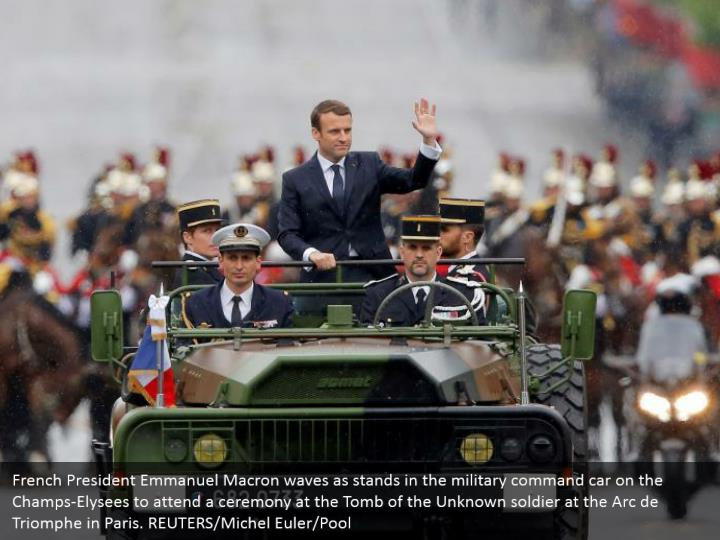 French president emmanuel macron waves as stands