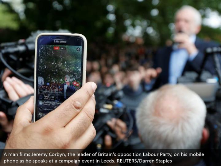 A man films Jeremy Corbyn, the leader of Britain's opposition Labour Party, on his mobile phone as he speaks at a campaign event in Leeds. REUTERS/Darren Staples