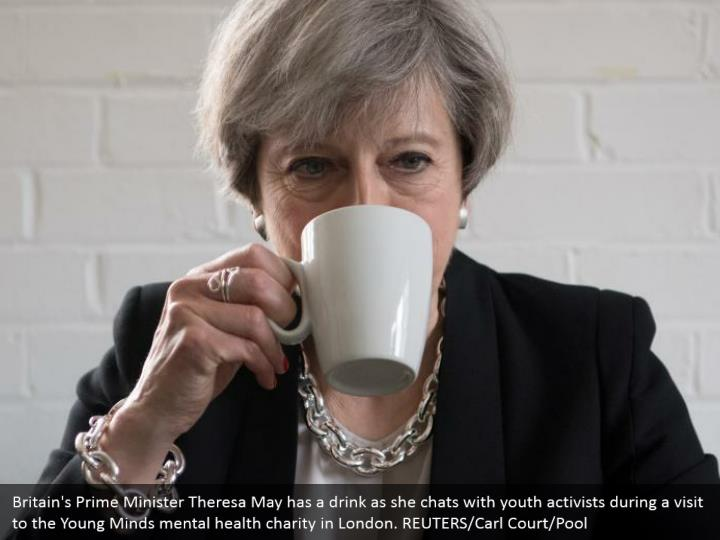 Britain's Prime Minister Theresa May has a drink as she chats with youth activists during a visit to the Young Minds mental health charity in London. REUTERS/Carl Court/Pool