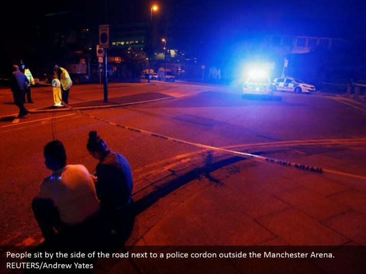 People sit by the side of the road next to a police cordon outside the Manchester Arena. REUTERS/Andrew Yates