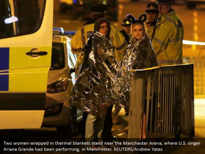 Two women wrapped in thermal blankets stand near the Manchester Arena, where U.S. singer Ariana Grande had been performing, in Manchester. REUTERS/Andrew Yates