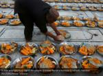 a man arranges food plates for people to break