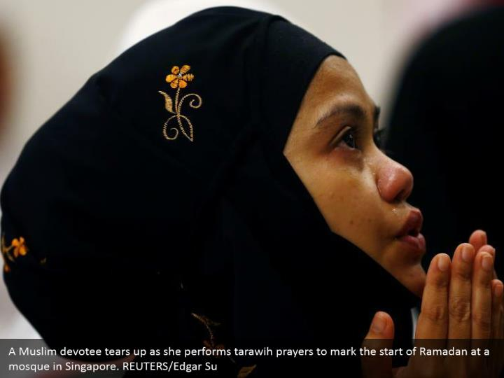 A Muslim devotee tears up as she performs tarawih prayers to mark the start of Ramadan at a mosque in Singapore. REUTERS/Edgar Su