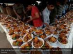men arrange food plates for passersby to break
