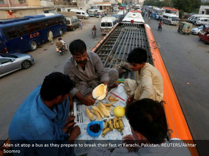 Men sit atop a bus as they prepare to break their fast in Karachi, Pakistan. REUTERS/Akhtar Soomro