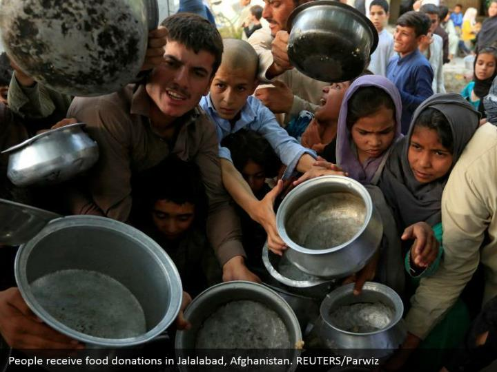 People receive food donations in Jalalabad, Afghanistan. REUTERS/Parwiz