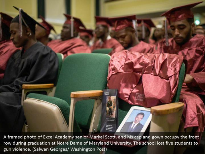 A framed photo of Excel Academy senior Markel Scott, and his cap and gown occupy the front row during graduation at Notre Dame of Maryland University. The school lost five students to gun violence. (Salwan Georges/ Washington Post)