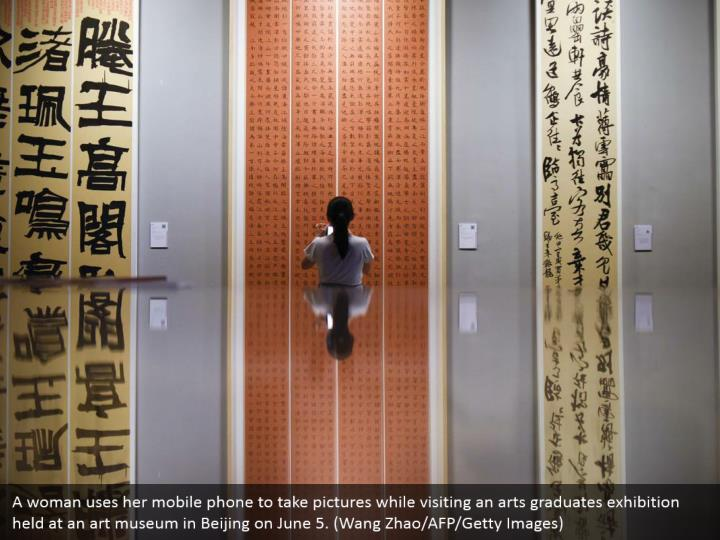 A woman uses her mobile phone to take pictures while visiting an arts graduates exhibition held at an art museum in Beijing on June 5. (Wang Zhao/AFP/Getty Images)