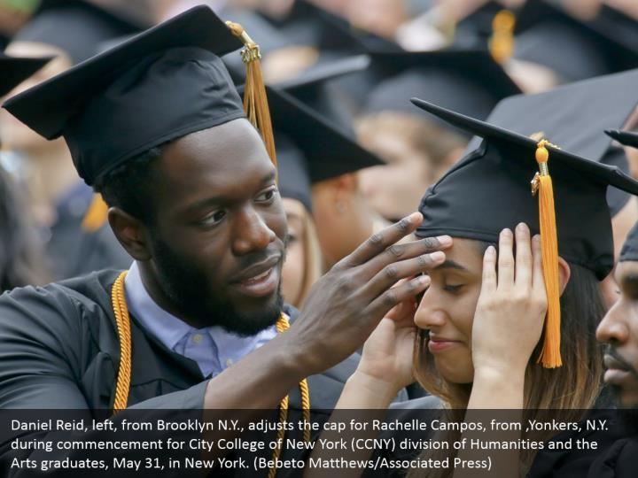 Daniel Reid, left, from Brooklyn N.Y., adjusts the cap for Rachelle Campos, from ,Yonkers, N.Y. during commencement for City College of New York (CCNY) division of Humanities and the Arts graduates, May 31, in New York. (Bebeto Matthews/Associated Press)