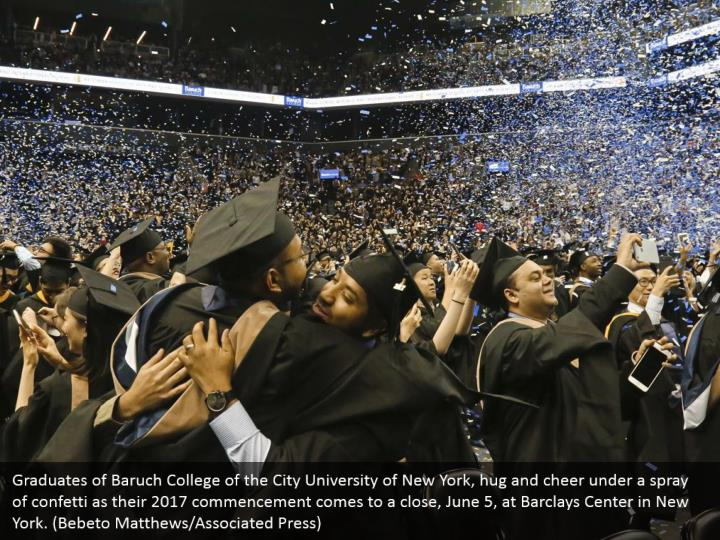 Graduates of Baruch College of the City University of New York, hug and cheer under a spray of confetti as their 2017 commencement comes to a close, June 5, at Barclays Center in New York. (Bebeto Matthews/Associated Press)