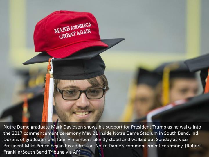 Notre Dame graduate Mark Davidson shows his support for President Trump as he walks into the 2017 commencement ceremony May 21 inside Notre Dame Stadium in South Bend, Ind. Dozens of graduates and family members silently stood and walked out Sunday as Vice President Mike Pence began his address at Notre Dame's commencement ceremony. (Robert Franklin/South Bend Tribune via AP)