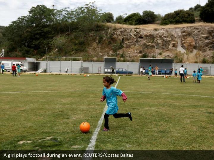 A girl plays football during an event. REUTERS/Costas Baltas