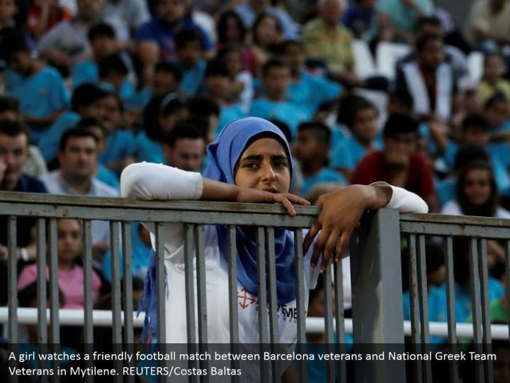 A girl watches a friendly football match between Barcelona veterans and National Greek Team Veterans in Mytilene. REUTERS/Costas Baltas