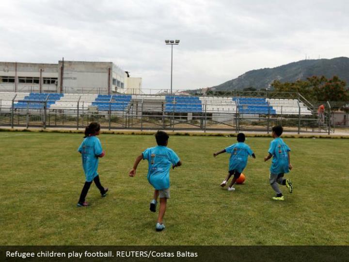 Refugee children play football. REUTERS/Costas Baltas