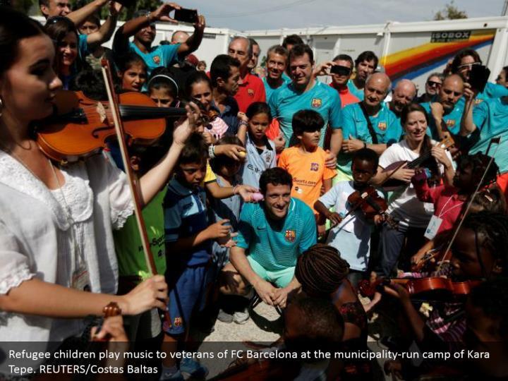 Refugee children play music to veterans of FC Barcelona at the municipality-run camp of Kara Tepe. REUTERS/Costas Baltas