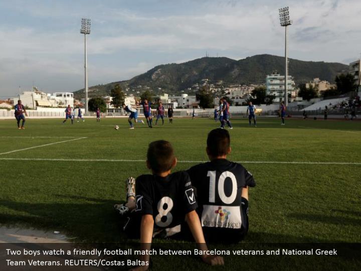 Two boys watch a friendly football match between Barcelona veterans and National Greek Team Veterans. REUTERS/Costas Baltas
