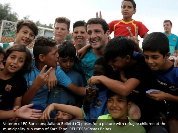 Veteran of FC Barcelona Juliano Belletti (C) poses for a picture with refugee children at the municipality-run camp of Kara Tepe. REUTERS/Costas Baltas