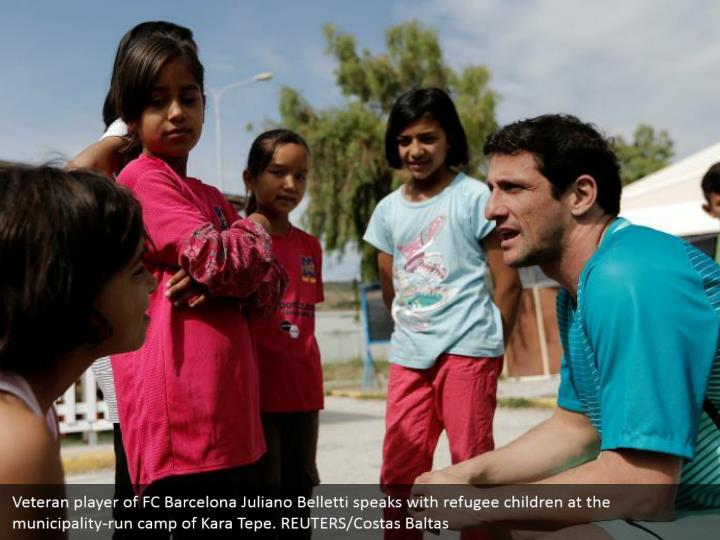 Veteran player of FC Barcelona Juliano Belletti speaks with refugee children at the municipality-run camp of Kara Tepe. REUTERS/Costas Baltas