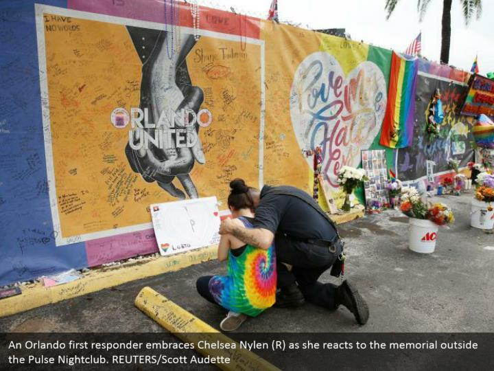 An Orlando first responder embraces Chelsea Nylen (R) as she reacts to the memorial outside the Pulse Nightclub. REUTERS/Scott Audette