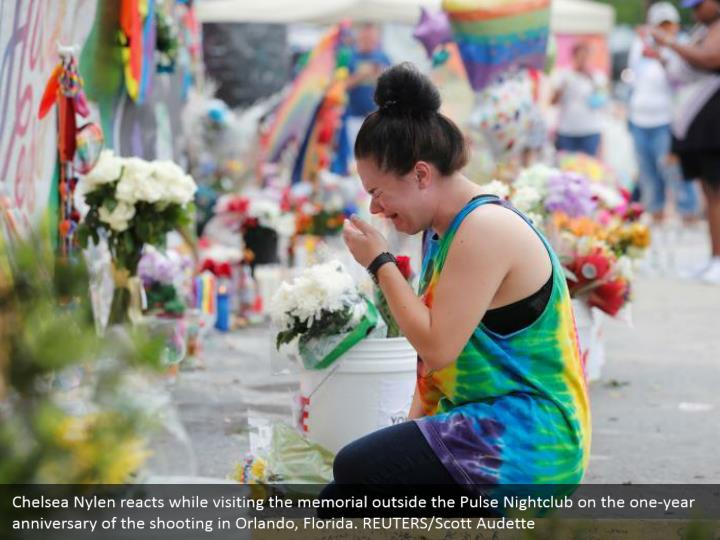 Chelsea Nylen reacts while visiting the memorial outside the Pulse Nightclub on the one-year anniversary of the shooting in Orlando, Florida. REUTERS/Scott Audette