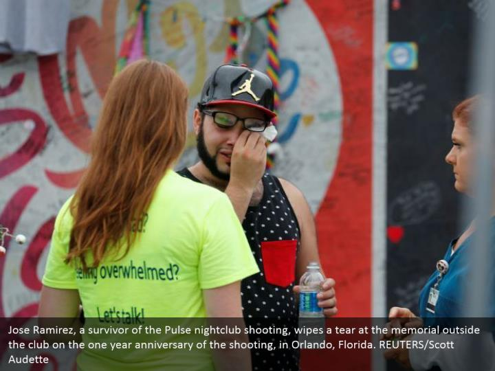 Jose Ramirez, a survivor of the Pulse nightclub shooting, wipes a tear at the memorial outside the club on the one year anniversary of the shooting, in Orlando, Florida. REUTERS/Scott Audette