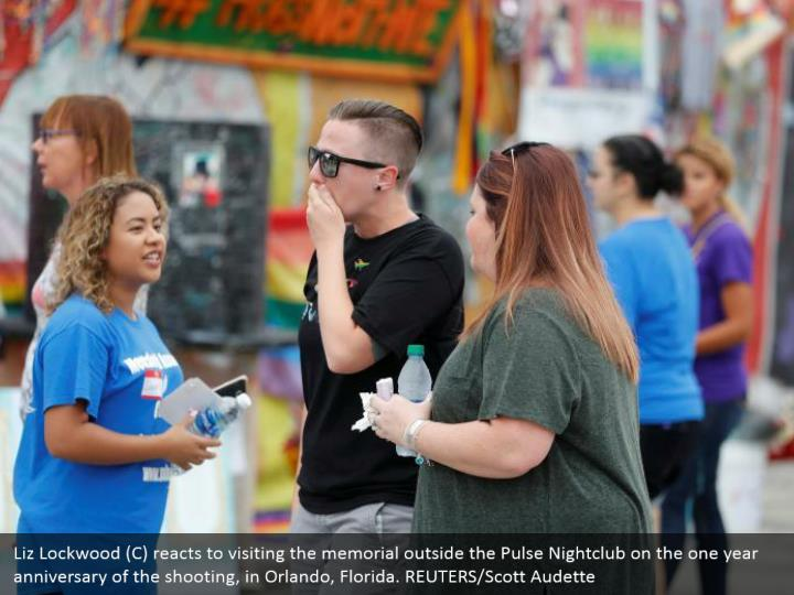 Liz Lockwood (C) reacts to visiting the memorial outside the Pulse Nightclub on the one year anniversary of the shooting, in Orlando, Florida. REUTERS/Scott Audette