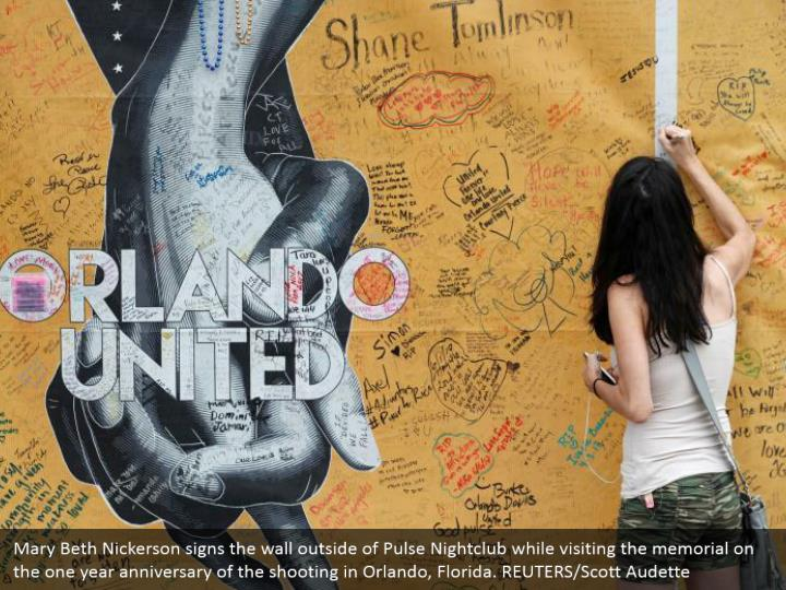 Mary Beth Nickerson signs the wall outside of Pulse Nightclub while visiting the memorial on the one year anniversary of the shooting in Orlando, Florida. REUTERS/Scott Audette