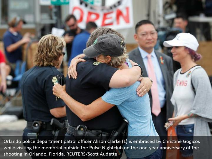 Orlando police department patrol officer Alison Clarke (L) is embraced by Christine Gogicos while visiting the memorial outside the Pulse Nightclub on the one-year anniversary of the shooting in Orlando, Florida. REUTERS/Scott Audette