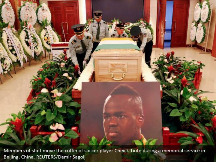 Members of staff move the coffin of soccer player Cheick Tiote during a memorial service in Beijing, China. REUTERS/Damir Sagolj