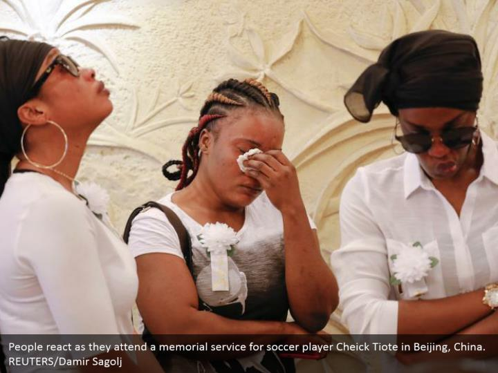 People react as they attend a memorial service for soccer player Cheick Tiote in Beijing, China. REUTERS/Damir Sagolj
