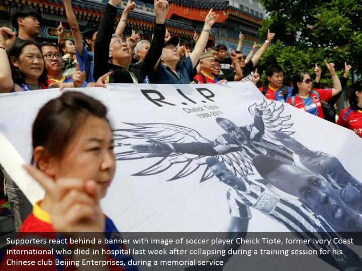 Supporters react behind a banner with image of soccer player Cheick Tiote, former Ivory Coast international who died in hospital last week after collapsing during a training session for his Chinese club Beijing Enterprises, during a memorial service