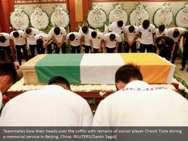 Teammates bow their heads over the coffin with remains of soccer player Cheick Tiote during a memorial service in Beijing, China. REUTERS/Damir Sagolj