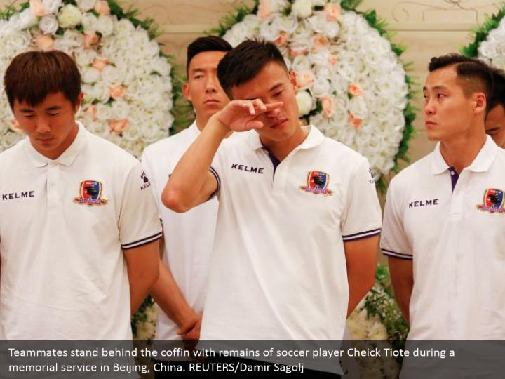 Teammates stand behind the coffin with remains of soccer player Cheick Tiote during a memorial service in Beijing, China. REUTERS/Damir Sagolj